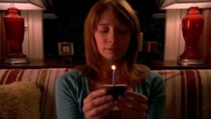 Still of a young woman sitting on a couch with her eyes closed and holding a cupcake with a lit candle.