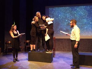 Picture shows a stage with a backdrop made to look like a star-filled sky. Three actors stand on a black box hugging each other. Two other actors stand to either side of the group, reading their lines.